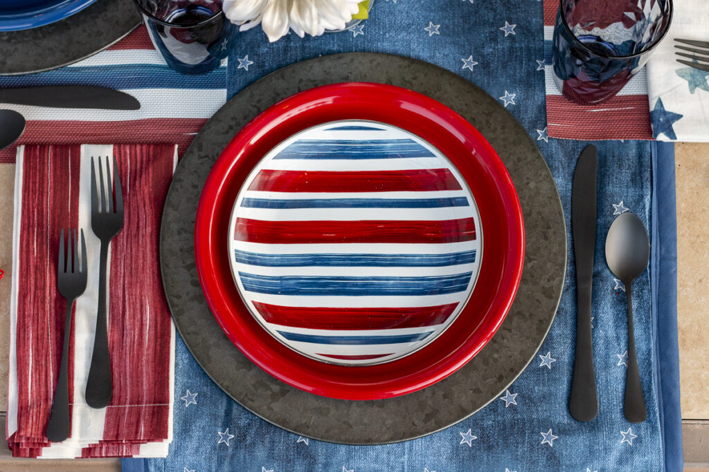 Americana place setting with red, white, and blue striped salad plate, on a red dinner plate, on a metal charger. Red and white napkins on a denim table runner.