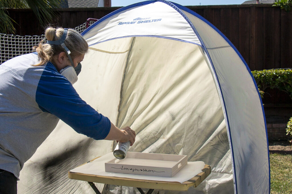 Woman spraying clear acrylic coating onto the Love You S'more tray inside a spray shelter