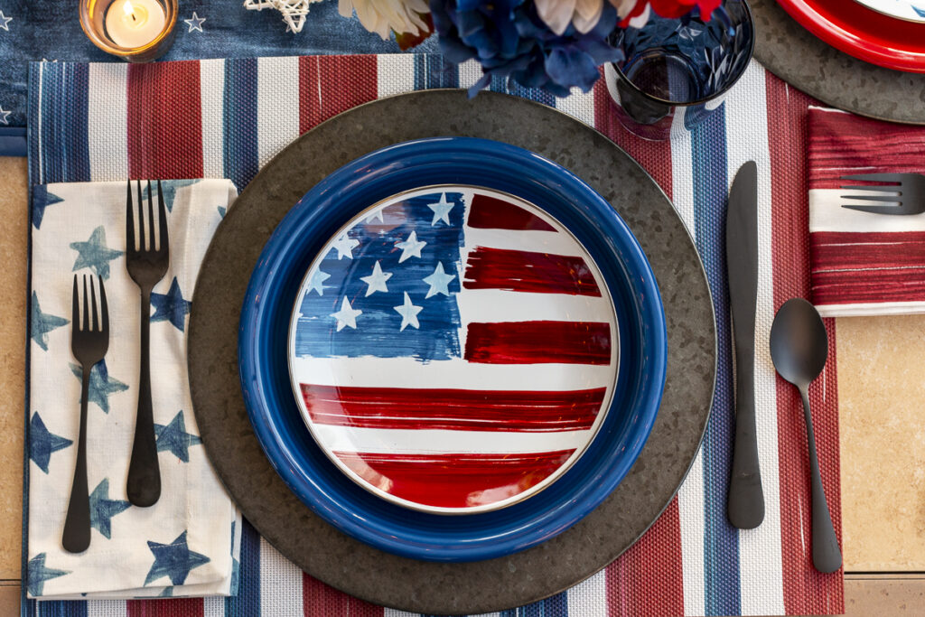Americana place setting with red, white, and blue flag salad plate, on a blue dinner plate, on a metal charger. A white napkin with blue stars on a red, white, and blue striped placemat.