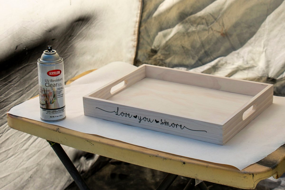 Can of Krylon UV-Resistant Clear Acrylic Coating on a table next to the Love You S'More tray inside a spray shelter