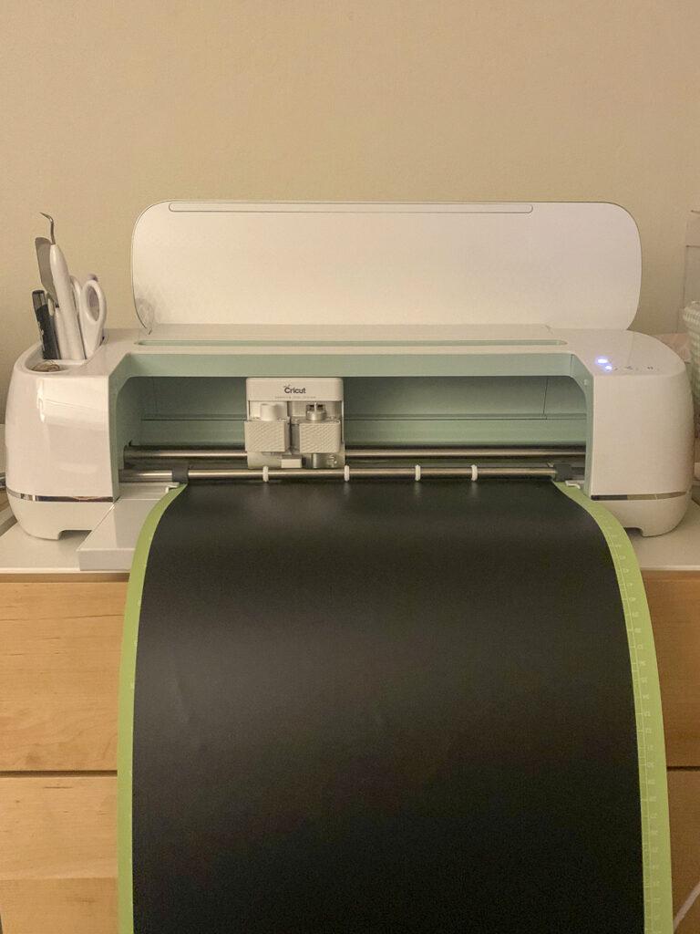 """Cricut Maker machine cutting a design out of a long piece of black vinyl stuck to 12"""" by 24"""" Cricut standard grip cutting mat."""