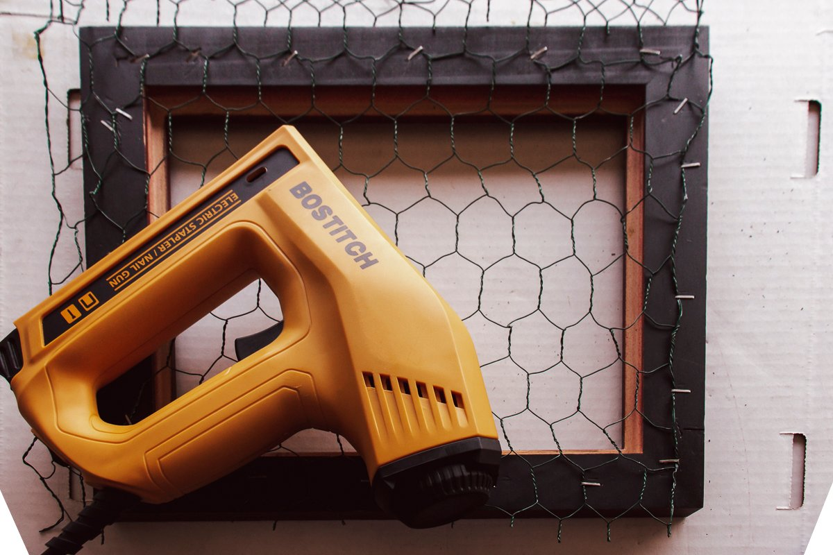 Electric stapler/nail gun sitting on chicken wire stapled to the back side of a picture frame.