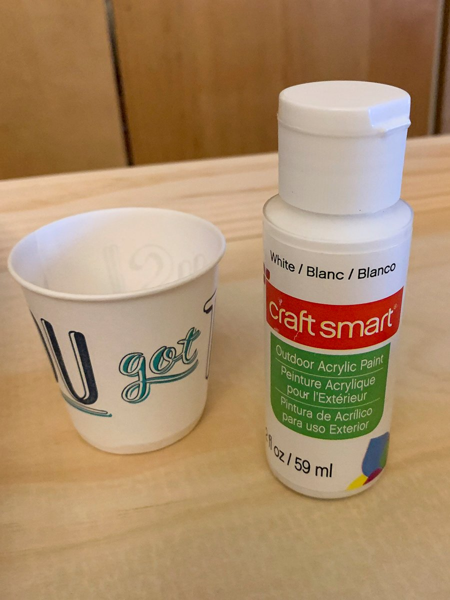 2 oz container of white acrylic craft paint and a small cup of water (the two items needed for creating a white-wash finish on wood).