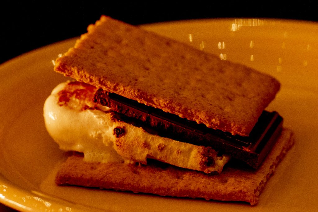 S'more on a plate consisting of two graham crackers, a square of chocolate and a toasted marshmallow.