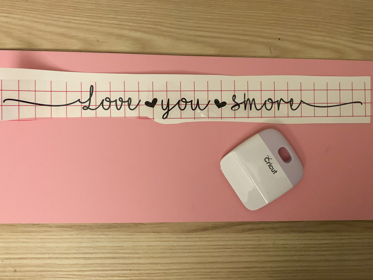 Piece of transfer tape over the top of a Love You S'more vinyl design and a Cricut scraping tool
