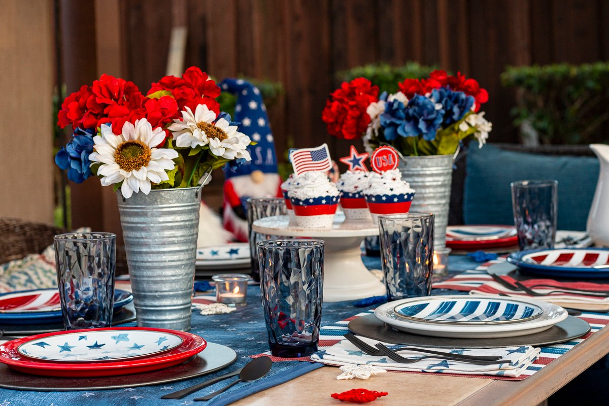 Patriotic table setting (stars and stripes enamel salad plates; red, white, & blue dinner plates; blue drinking glasses; patriotic flowers in tin vases; and festive cupcakes on a cake stand).