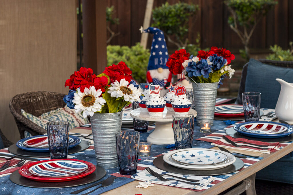 Patriotic garden gnome overlooking red, white, and blue table settings with festive cupcakes and flowers.