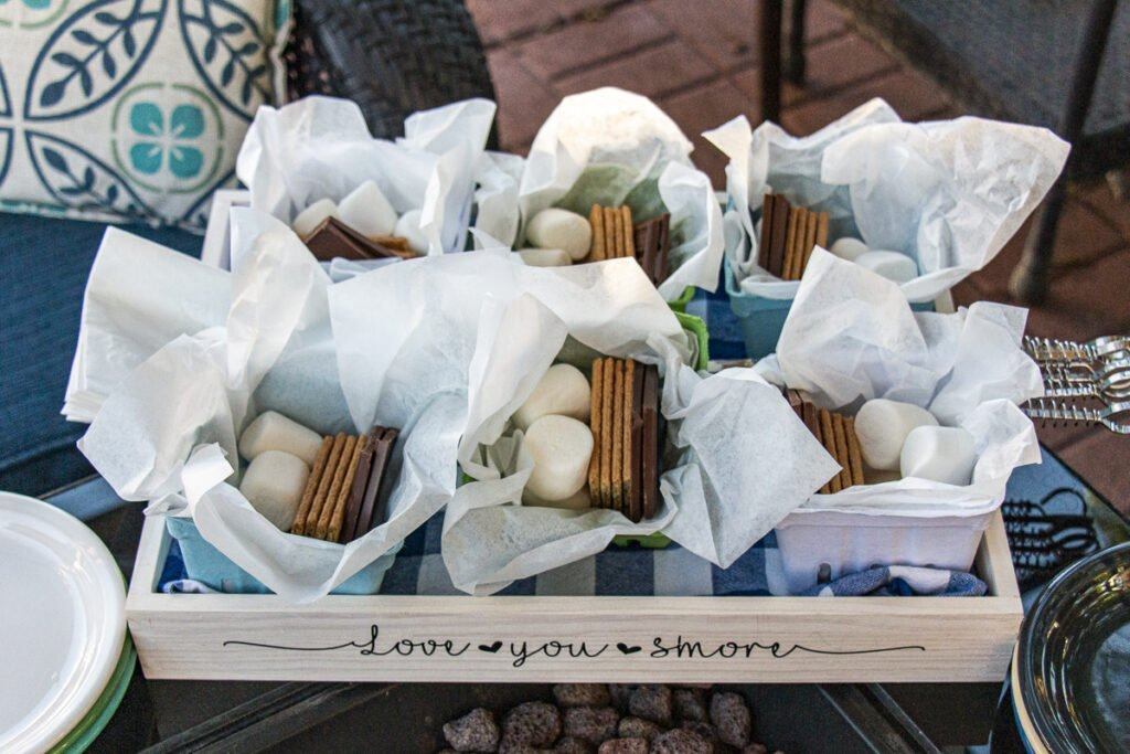 """Overhead view of wood tray with the phrase """"Love you S'more"""" with holding 6 individual s'more kits consisting of marshmallows, chocolate squares, and graham crackers on a S'more Serving Tray with napkins and toasting sticks"""