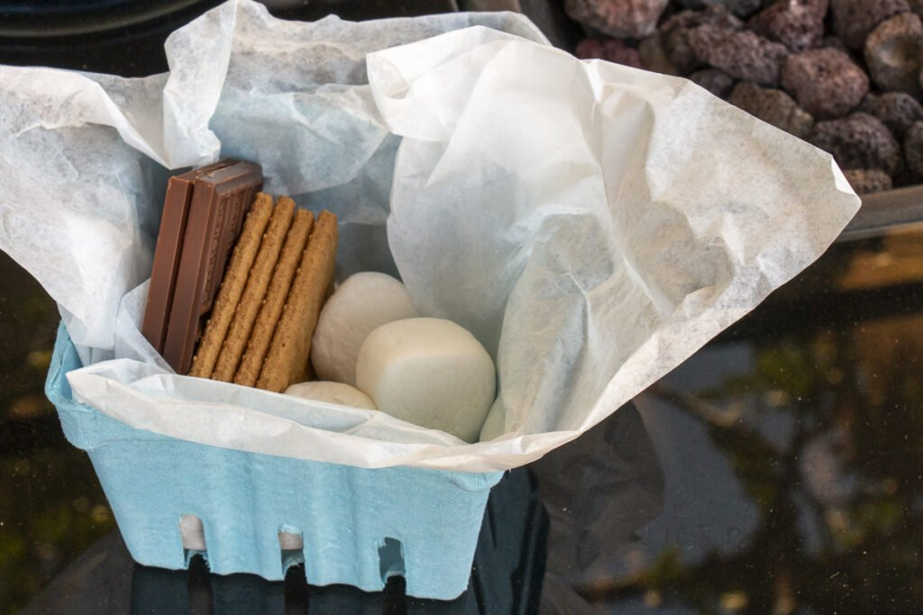 S'more serving kit consisting of a paper berry basket lined in deli paper with chocolate bars, graham crackers, and marshmallows