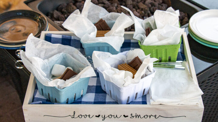 4 berry baskets with individual s'more kits consisting of marshmallows, chocolate squares, and graham crackers on a S'more Serving Tray with napkins and toasting sticks