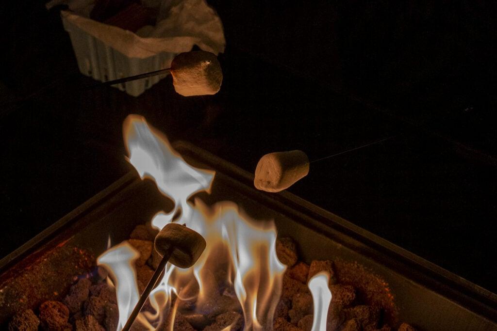 Three marshmallows on sticks roasting over flames
