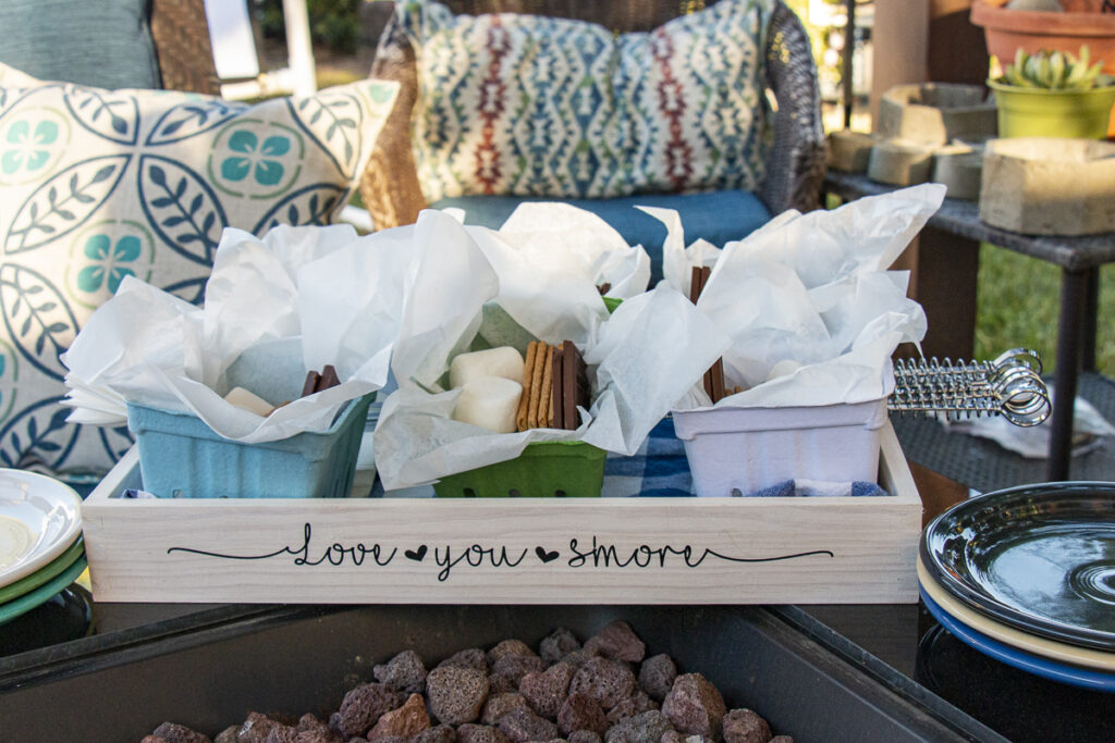 """Side of wood tray with the phrase """"Love you S'more"""" with holding 6 individual s'more kits consisting of marshmallows, chocolate squares, and graham crackers on a S'more Serving Tray with napkins and toasting sticks. Tray is next to a fire pit and snack plates."""