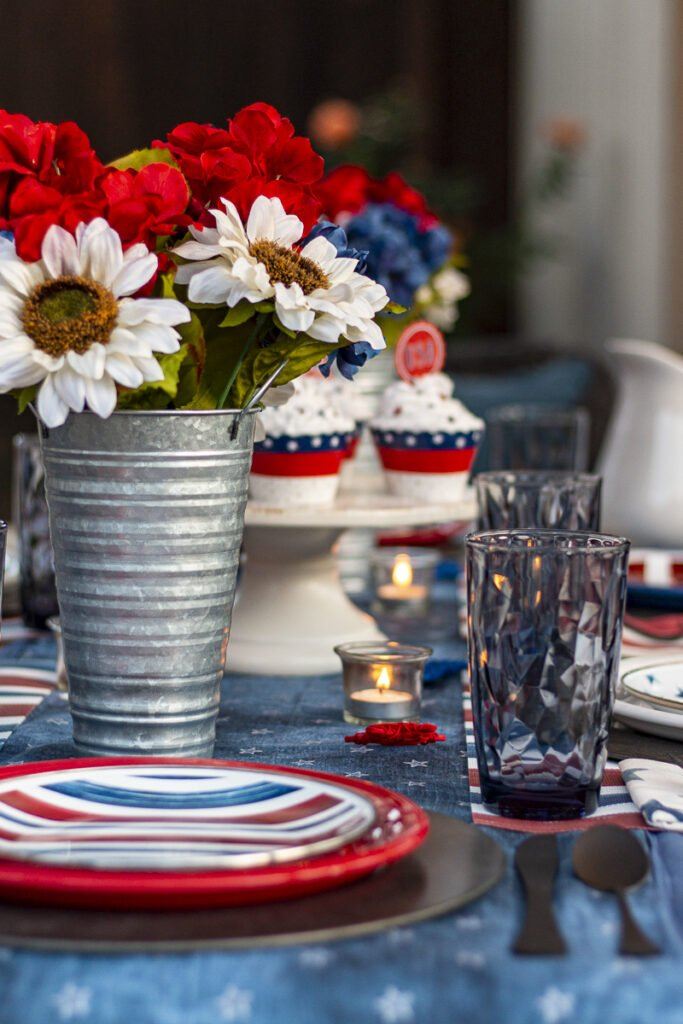 Patriotic table setting (stars and stripes enamel salad plates; red, white, & blue dinner plates; blue drinking glasses; patriotic flowers in tin vases; tea lights; and festive cupcakes on a cake stand).