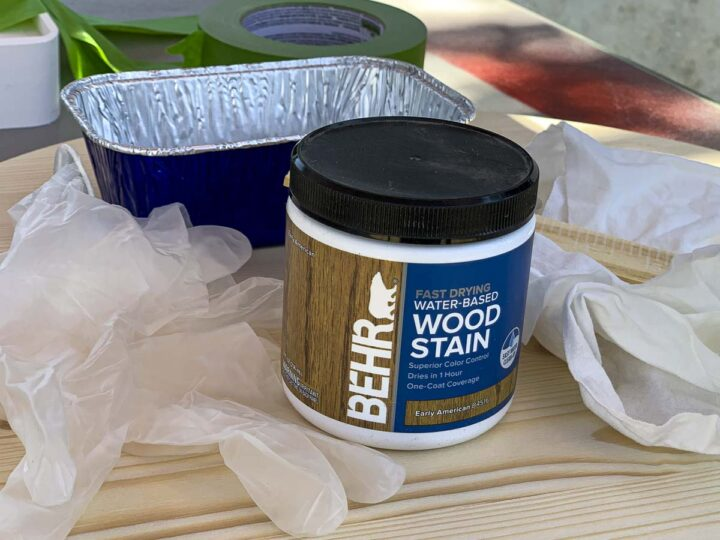 Small container of Behr Wood Stain and supplies needed to stain the wood, including plastic gloves, painter's tape, a white cloth and a tin tray.