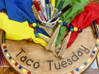 Round wood Lazy Susan taco tray with handles decorated the text Taco Tuesday and Fiesta! and a multi-colored pom pom banner around the edge. Colorful napkins with matching napkin rings and a painted planter filled with COLORSHOT markers are sitting on the tray..