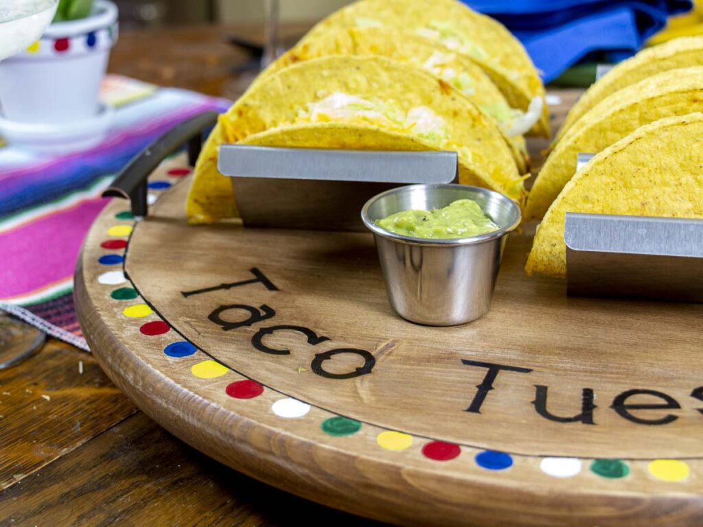 Close up shot of the edge of a Taco Tuesday Serving Tray containing tacos and guacamole.