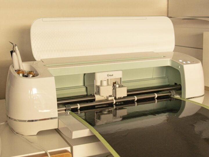 Cricut Maker electronic cutting machine cutting a stencil out of vinyl.
