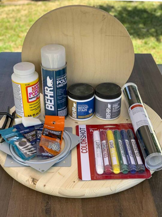 Materials for making the DIY Taco Tray (including wood rounds, handles, Lazy Susan swivel plate, vinyl for creating stencils, wood stain, paint and sealer).