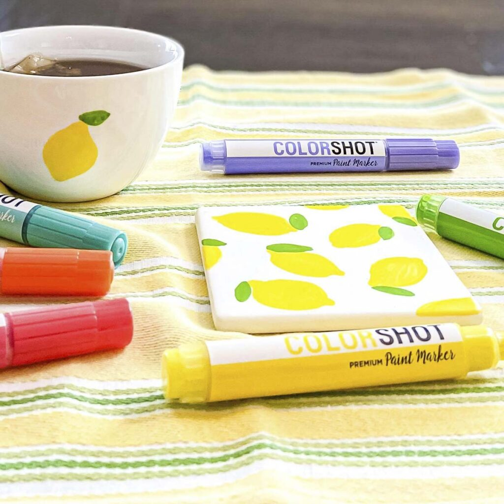 Pastel COLORSHOT premium markers around a tea-cup and a square tile decorated with painted lemons
