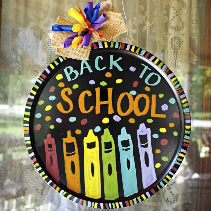 Pizza tray back-to-school wreath decorated with colorful painted crayons, polka dots, and a boy