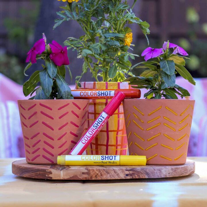 Three flower pots decorated with COLORSHOT premium paint markers