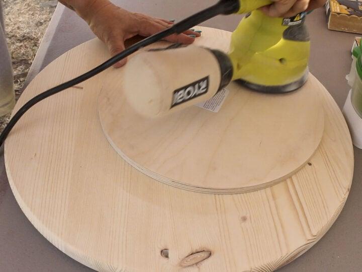 Sanding the wood rounds with a random orbit sander