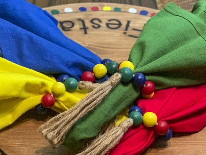 Napkin rings made of painted wood beads with tassels on colorful napkins.