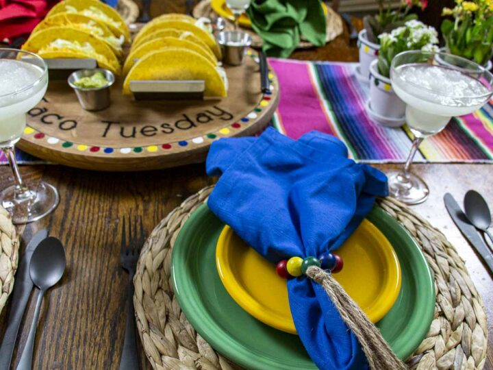 Taco Night Tablescape with a festive table runner, colorful dishes and napkins, and a Taco Tuesday serving tray