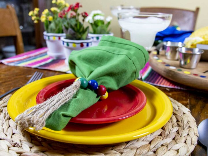 Taco Tuesday Tablescape place setting with colorful plates, napkins, and napkin rings. Matching centerpieces and taco tray nearby on the table.