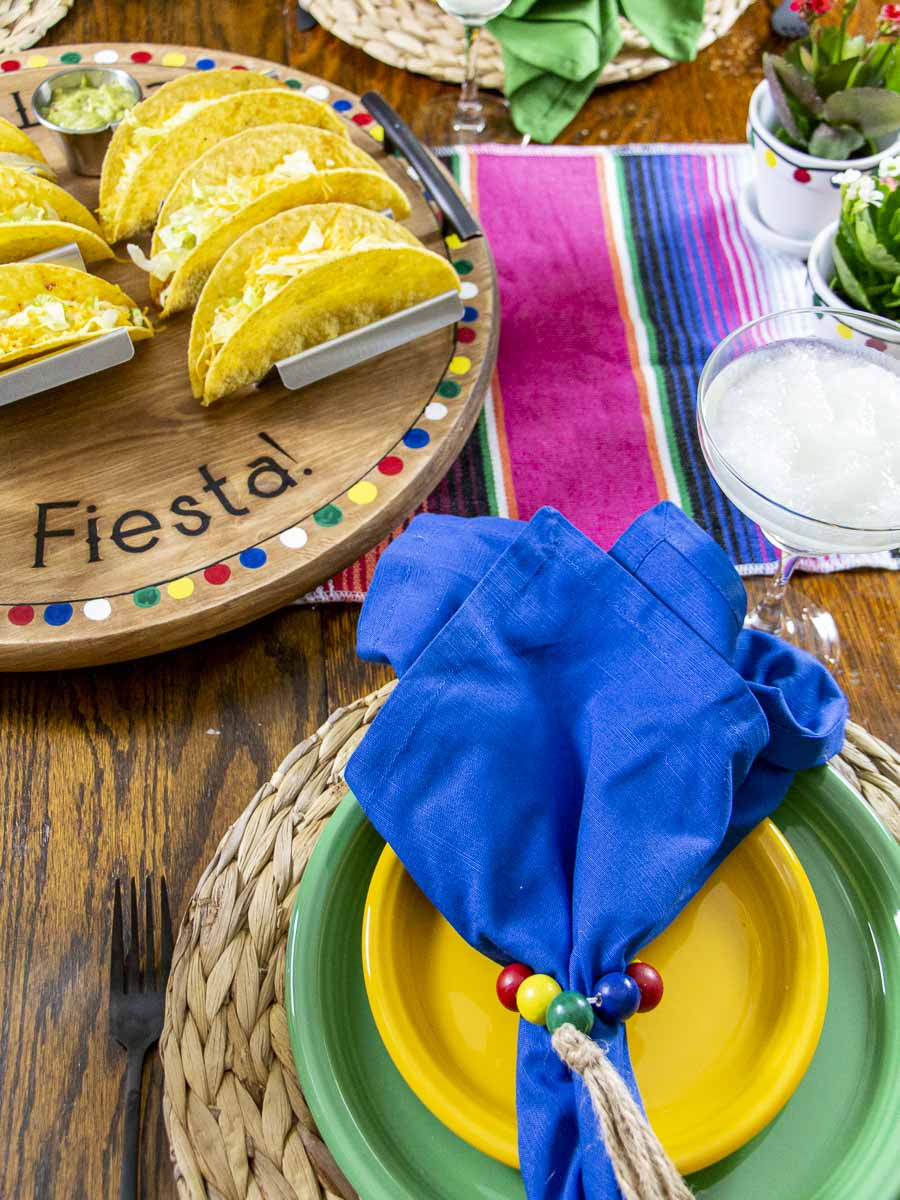 Taco Night Tablescape with a festive table runner, centerpieces, colorful dishes and napkins, and a Taco Tuesday serving tray