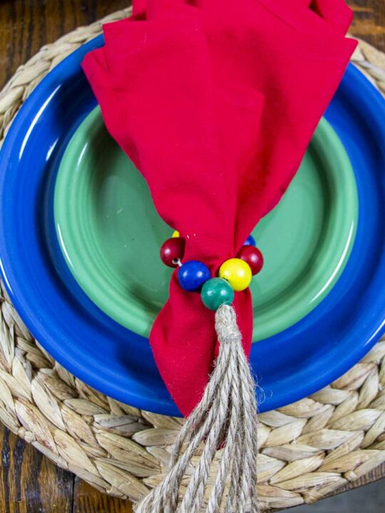 Taco Tuesday Tablescape place setting with colorful plates, napkins, and napkin rings.