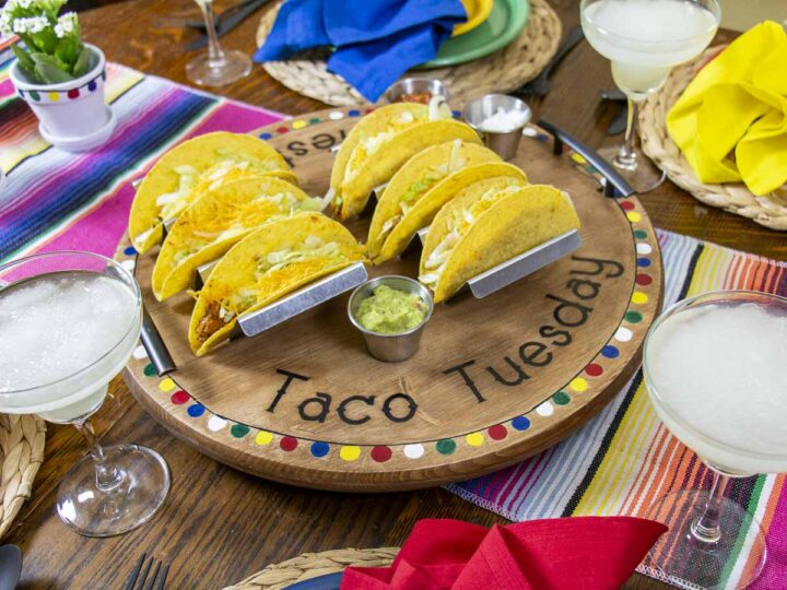 Taco Night Tablescape with festive table runner, margaritas, and serving platter full of tacos. The platter contains a Stainless Steel Taco Stand Set.