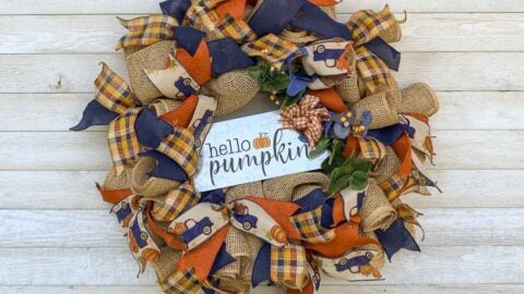 Fall wreath with poly-burlap-mesh decorated with blue, orange, and tan ribbons (including one with a blue truck with a bed of pumpkins). Includes a metal hello pumpkin sign.