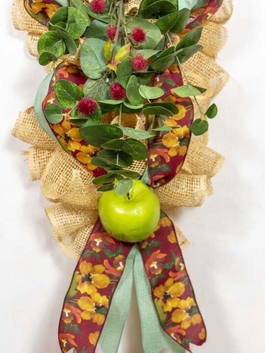 A fall swag made of poly burlap mesh decorated with ribbons, apples and flowers in autumn colors.