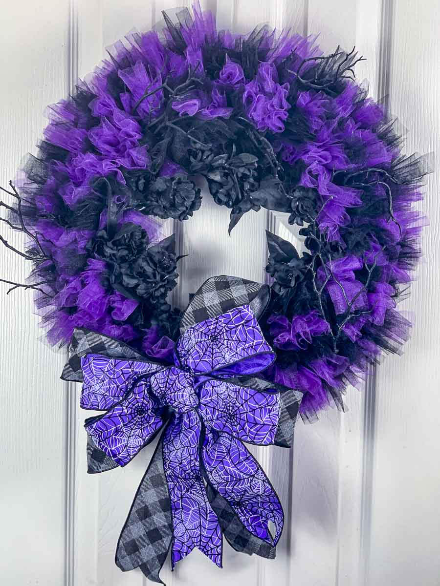 Black and Purple Halloween wreath made of tulle with a large bow with black and grey plaid ribbon and purple, black and white spiderweb ribbon.