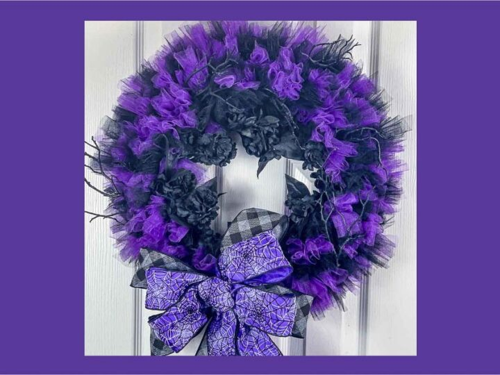 Black and purple tulle wreath with black flowers and a spider web bow