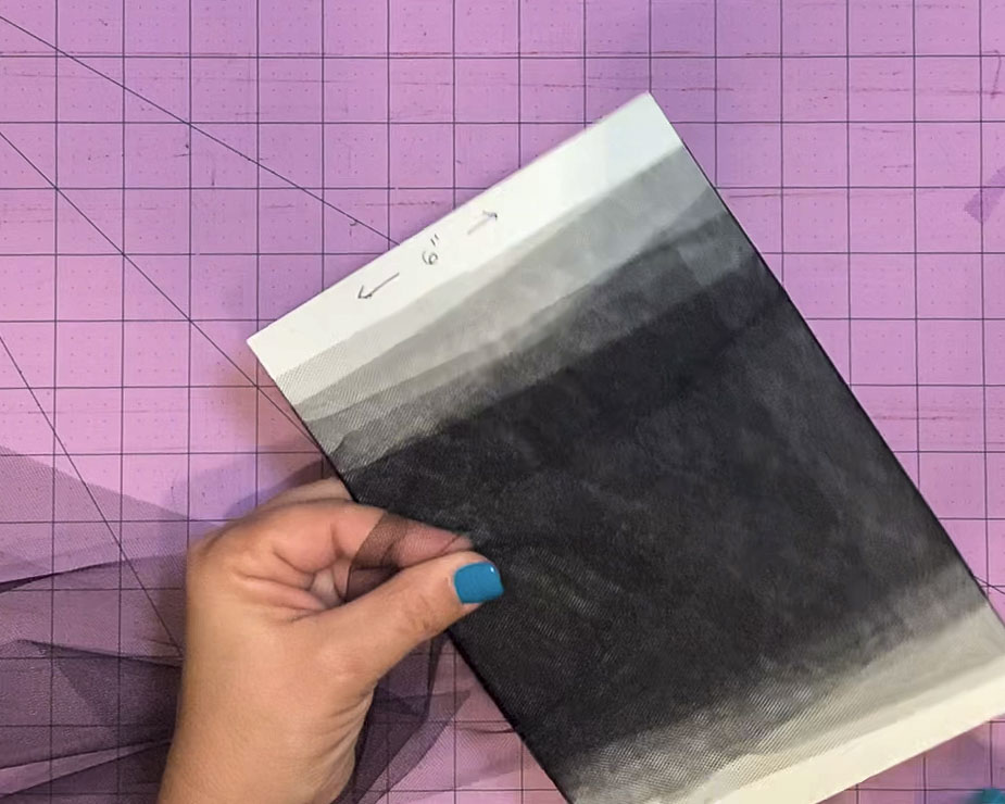 """6"""" wide and about 8"""" wide piece of cardboard with a strip of 6"""" wide tulle being wrapped around the cardboard to facilitate cutting tulle squares."""