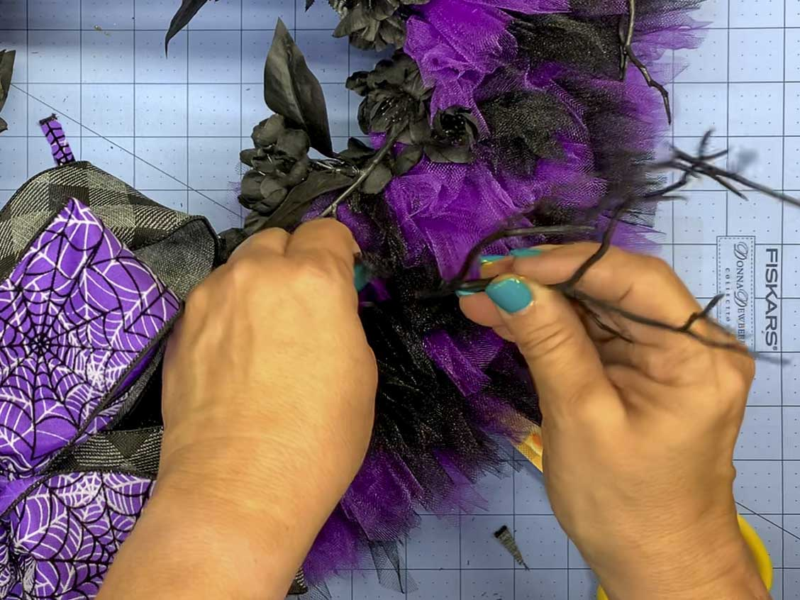 Embellishing the Halloween wreath by inserting small pieces of black plastic twigs between the pieces of tulle.