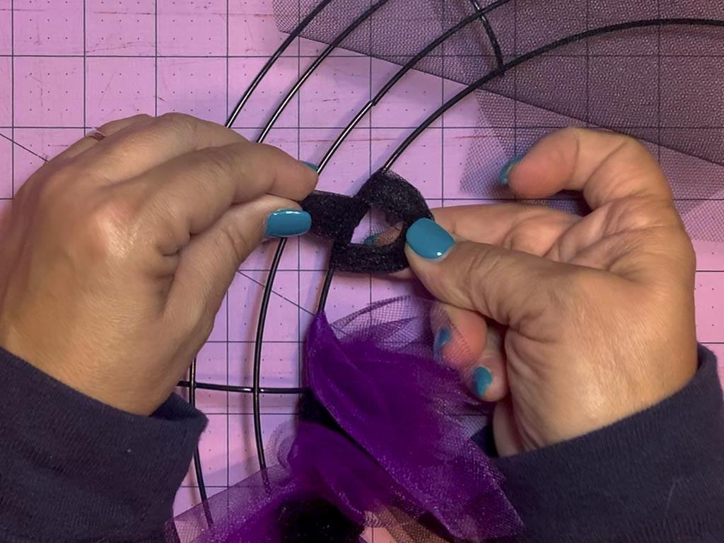 Two hands pulling the tail of tulle through the loop in the process of tying a tulle slip knot on a wreath form.
