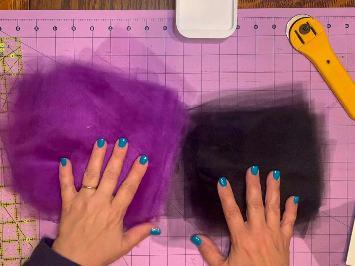 """Two stack of 6"""" square pieces of black and purple tulle that will be used to create a tulle wreath."""