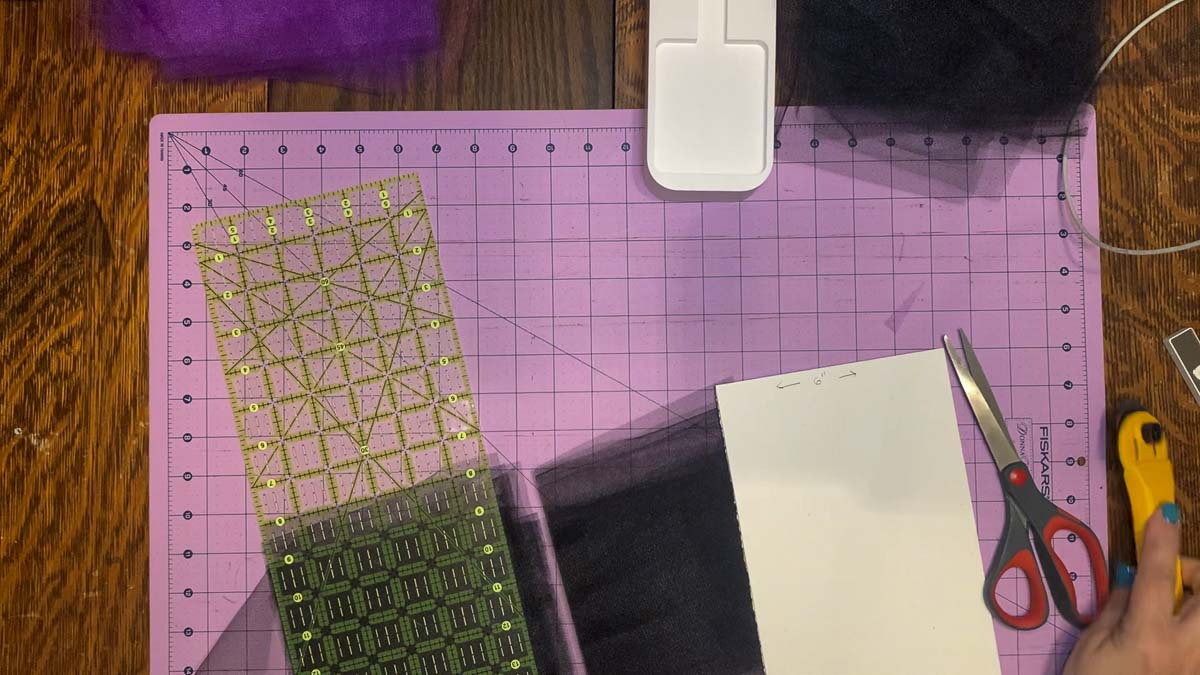 """Two stacks of 6"""" squares that have been cut from a length of tulle wrapped around a piece of cardboard to facilitate the process."""