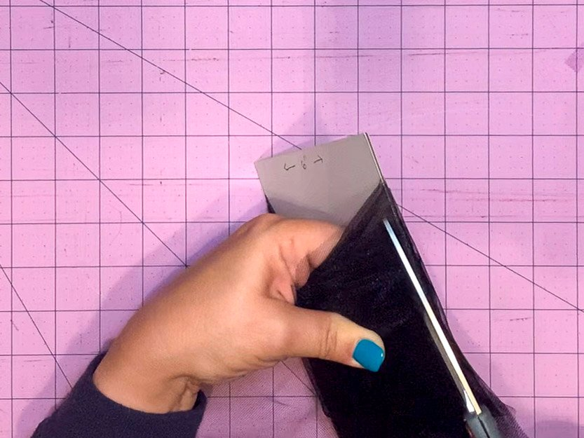 """Using a pair of scissors to cut along one side of a strip of tulle that had been wrapped around a 6"""" piece of cardboard. This will create 6"""" squares once both sides have been cut."""