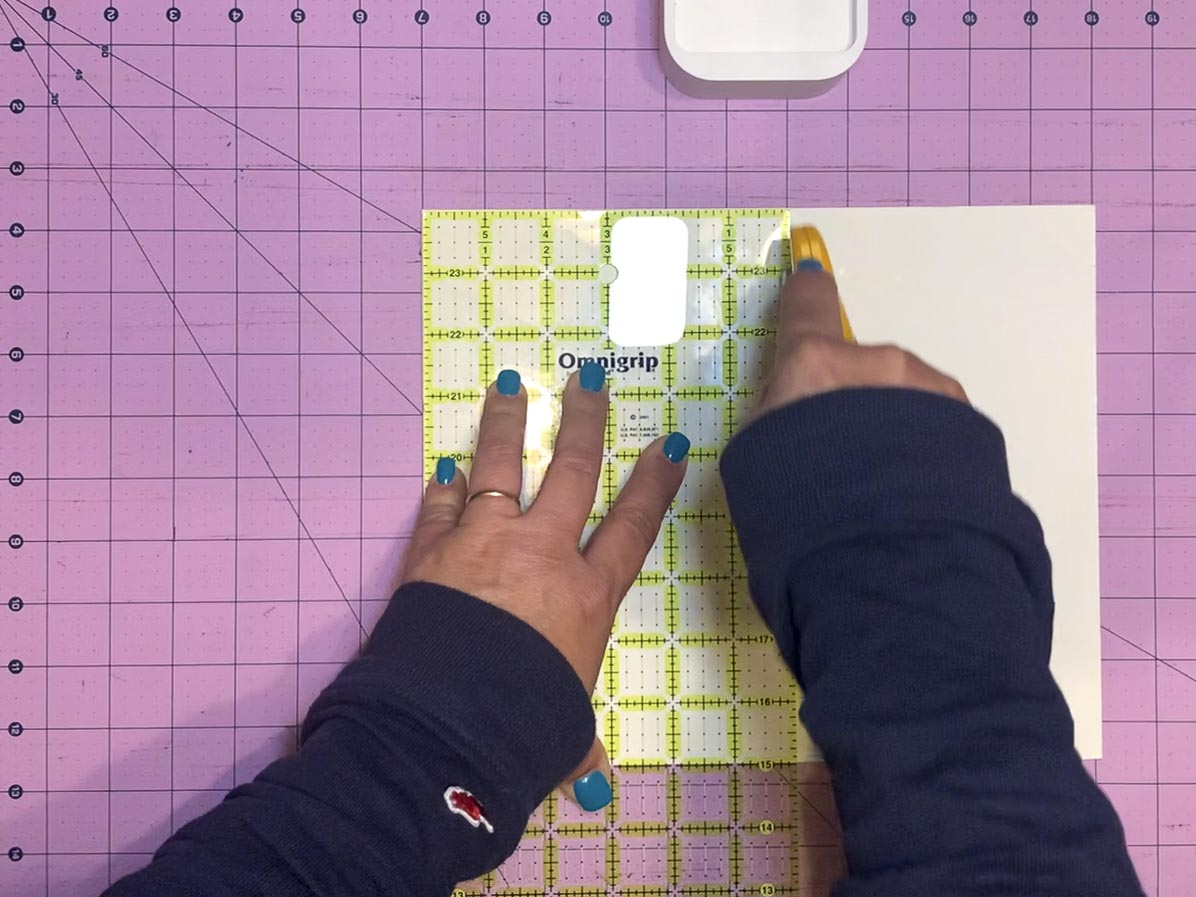 """Using a grid ruler and rotary cutter to cut a 6"""" wide piece of cardboard from a larger piece of cardboard."""