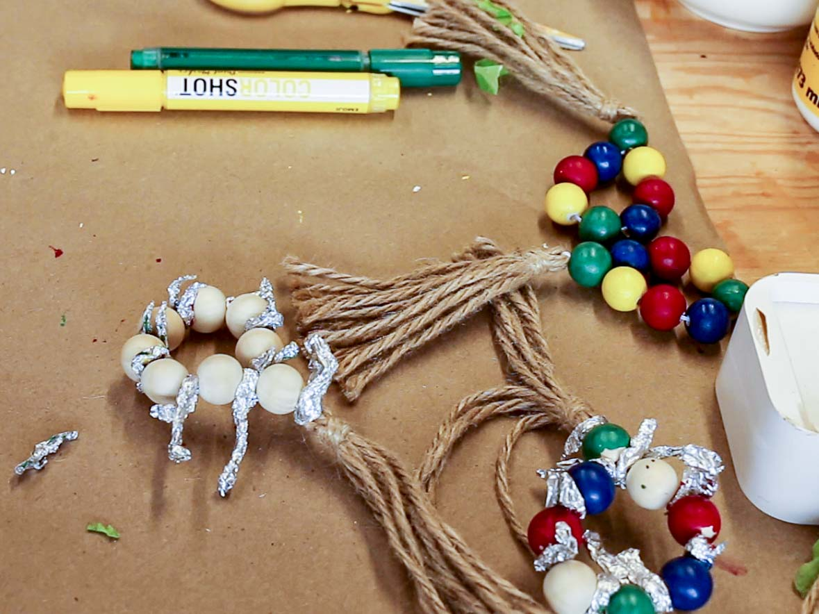 Wood bead napkin rings with jut tassels. Some rings are fully painted in bright colors. The beads on the unpainted and partially-painted rings are separated by rolled up pieces of foil.