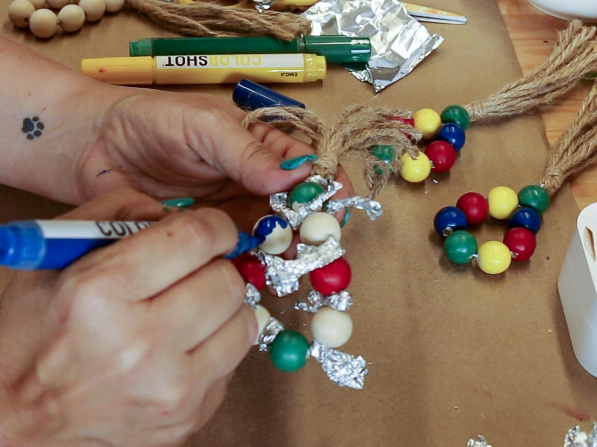 Hands using a blue COLORSHOT premium marker to paint a wood bead on a napkin ring.