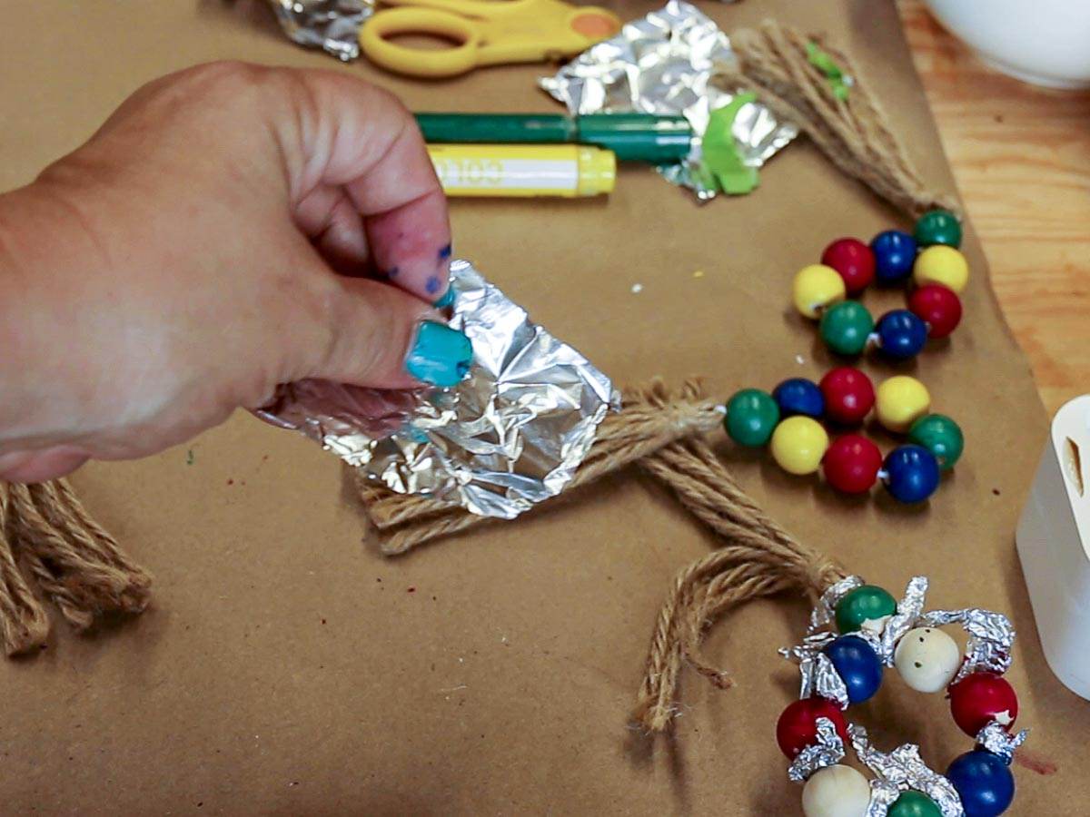Hand holding a small piece of foil to be used to separate wood beads while they are being painted.