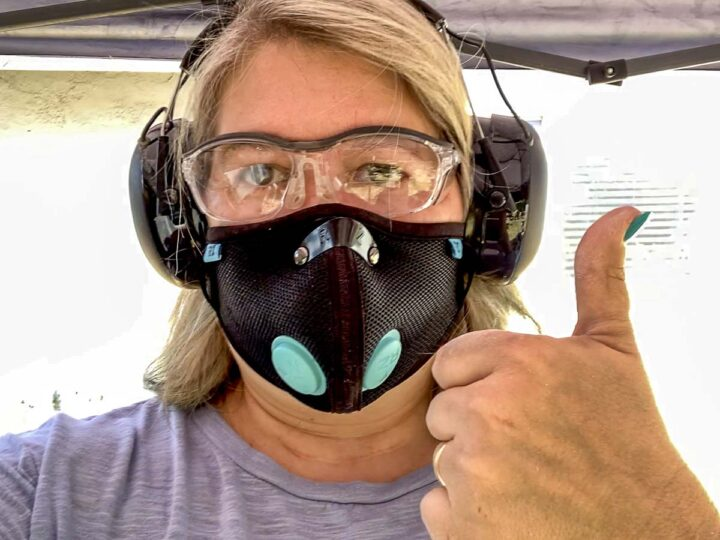 Person wearing safety classes, a dust mask and hearing protection. This personal protection equipment helps protect the user when sanding wood.