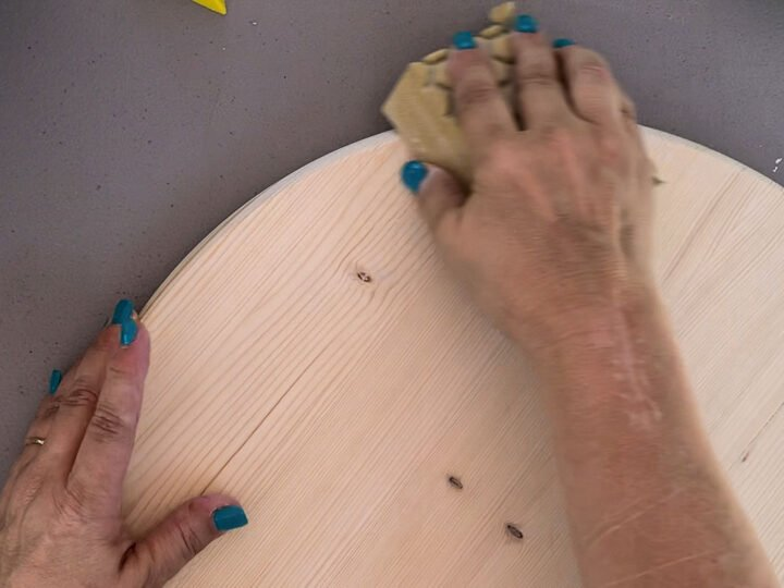 Sanding edges of wood round with a sanding sponge.