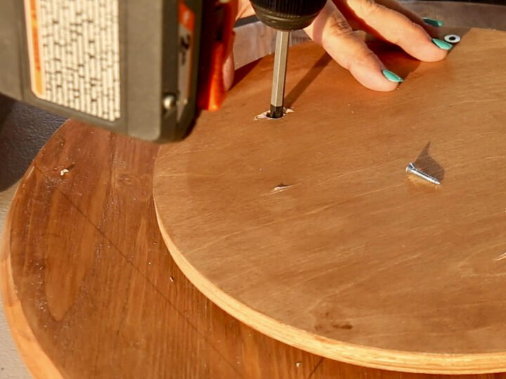 Attaching the Lazy Susan hardware to the underside of the top board by inserting a screw and washer through the access hole in the bottom of the base board.