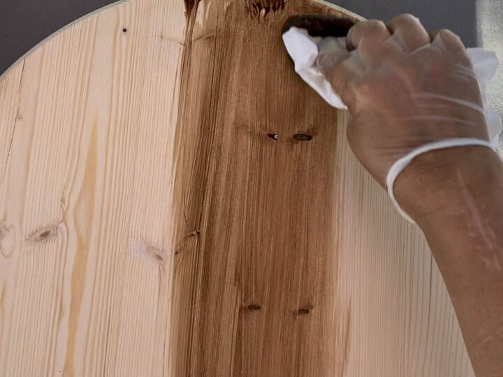 Applying stain to wood using a clean cloth.